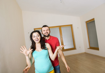Pregnant mother and happy father in new house