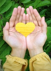 yellow heart on the hand