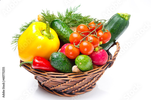 assorted fresh vegetables and herbs in a basket on white