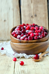 Cranberries in a wooden bowl on a wooden table