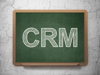 Business concept: CRM on chalkboard background