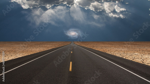 Road leads into desert toward galaxy above horizon - 60777039