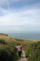 Walker on coastal path above Cardigan Bay