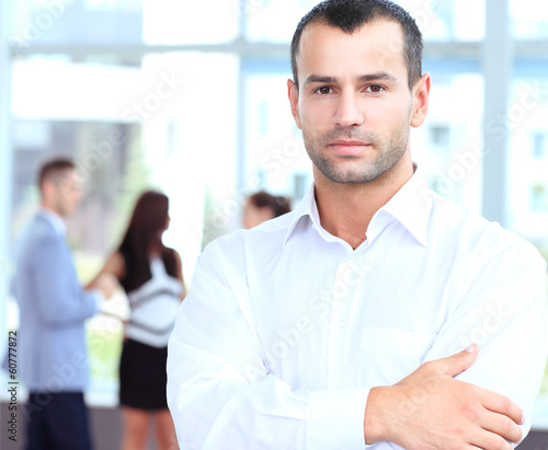 confident young businessman standing arms crossed, smiling happy