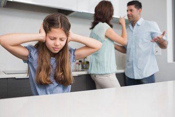 Sad girl covering ears while parents quarreling in kitchen