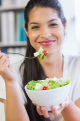 Businesswoman with salad bowl and fork