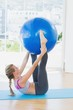 Woman holding exercise ball between ankles in fitness studio