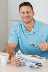 Man with newspaper having breakfast at table