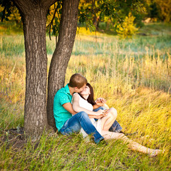 young couple kissing under a tree