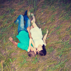 loving couple lying on the grass, top view