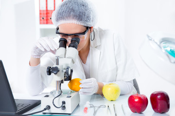 Female scientist looking through a microscope GMO lemon