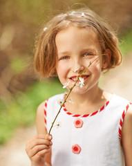 Mädchen riecht an Zweig eines Kirschbaums