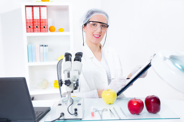 Young female scientist  in laboratory with GMO apple