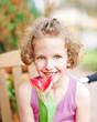Mädchen lächelt mit roter Tulpe