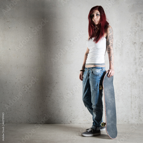 Full body woman portrait with skateboard against concrete wall.