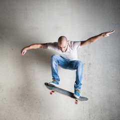 Skateboarder jumping against concrete wall.