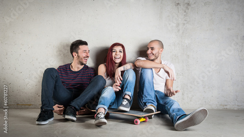 Happy friends portrait with skateboard against concrete wall.
