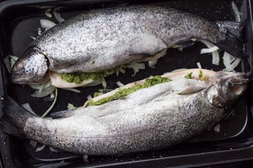 Cooking two fish, rainbow trout stuffed with green sauce