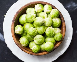Brussels sprouts in a wooden bowl on the table, tasty, healthy