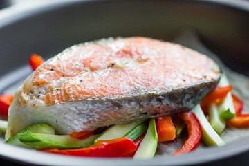 Cooking steak of red fish salmon on vegetables, zucchini, sweet
