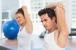 Sporty people stretching hands at yoga class