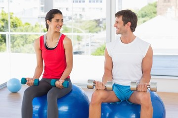 Happy couple lifting dumbbells while sitting on fitness balls