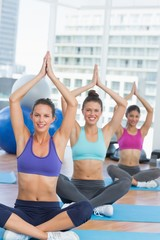 Smiling people in Namaste position at fitness studio
