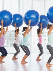 Fit women holding blue fitness balls in exercise room