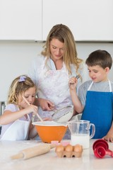 Children with mother baking cookies at counter top