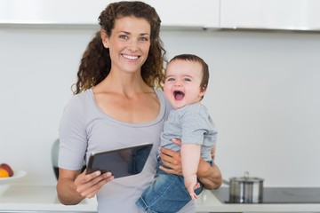 Happy mother with tablet carrying cheerful baby