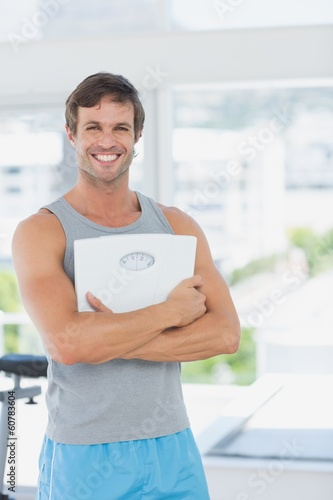 Fit man standing with scale in bright exercise room
