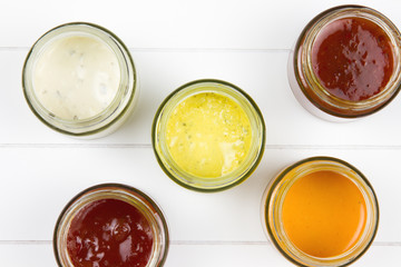 top-view of five jars filled with sauces