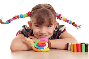 little girl make snail with plasticine