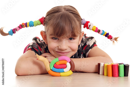 little girl make snail with plasticine