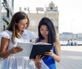 Portrait of two student girls with notes outside