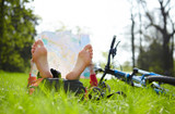 Cyclist reads a map lying barefoot on green grass outdoors in su