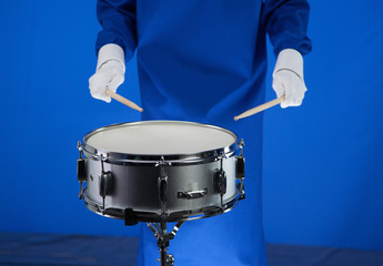 Drum and drumsticks in hand on blue background