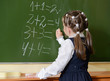 little schoolgirl writing on blackboard