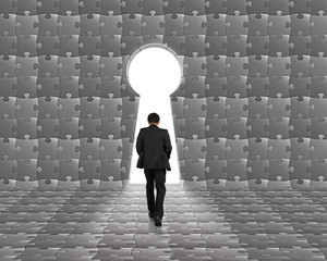 Businessman walking toward key shape door on puzzle wall