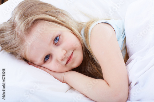 Kid girl lie on bed.