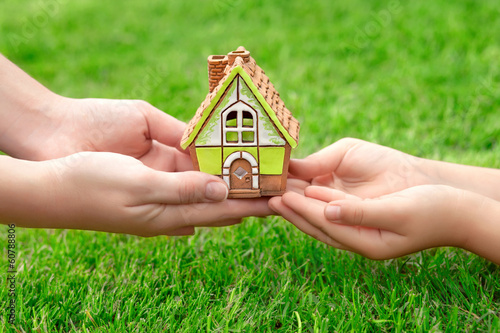 Hands mother and a child holding a little house on a background