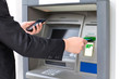 businessman inserts a credit card into the ATM to withdraw money