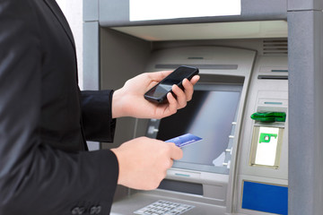 businessman standing near the ATM and holding a credit card and