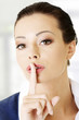 Portrait of attractive business woman with finger on lips