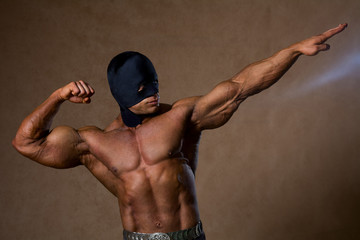 Strong muscular man in black mask
