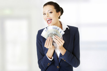 Happy businesswoman holding euros