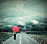 Lonesome man with red umbrella on a road in bad weather poster