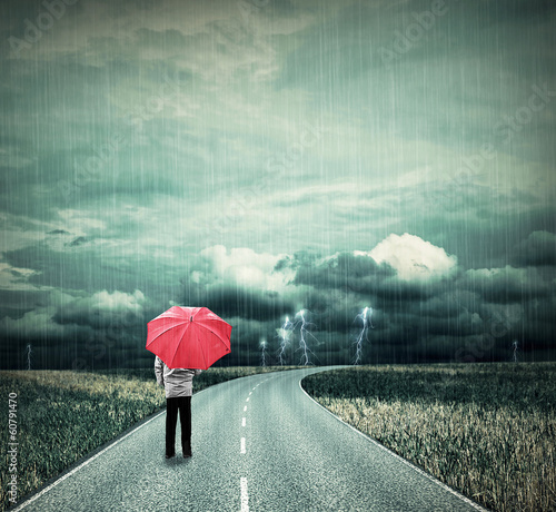 Lonesome man with red umbrella on a road in bad weather