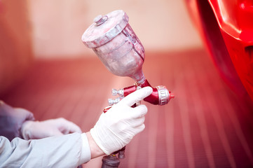 Worker painting a red car in paiting booth