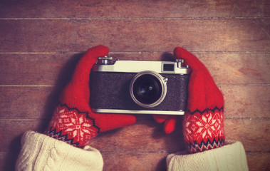 Hands in mittens holding vintage camera